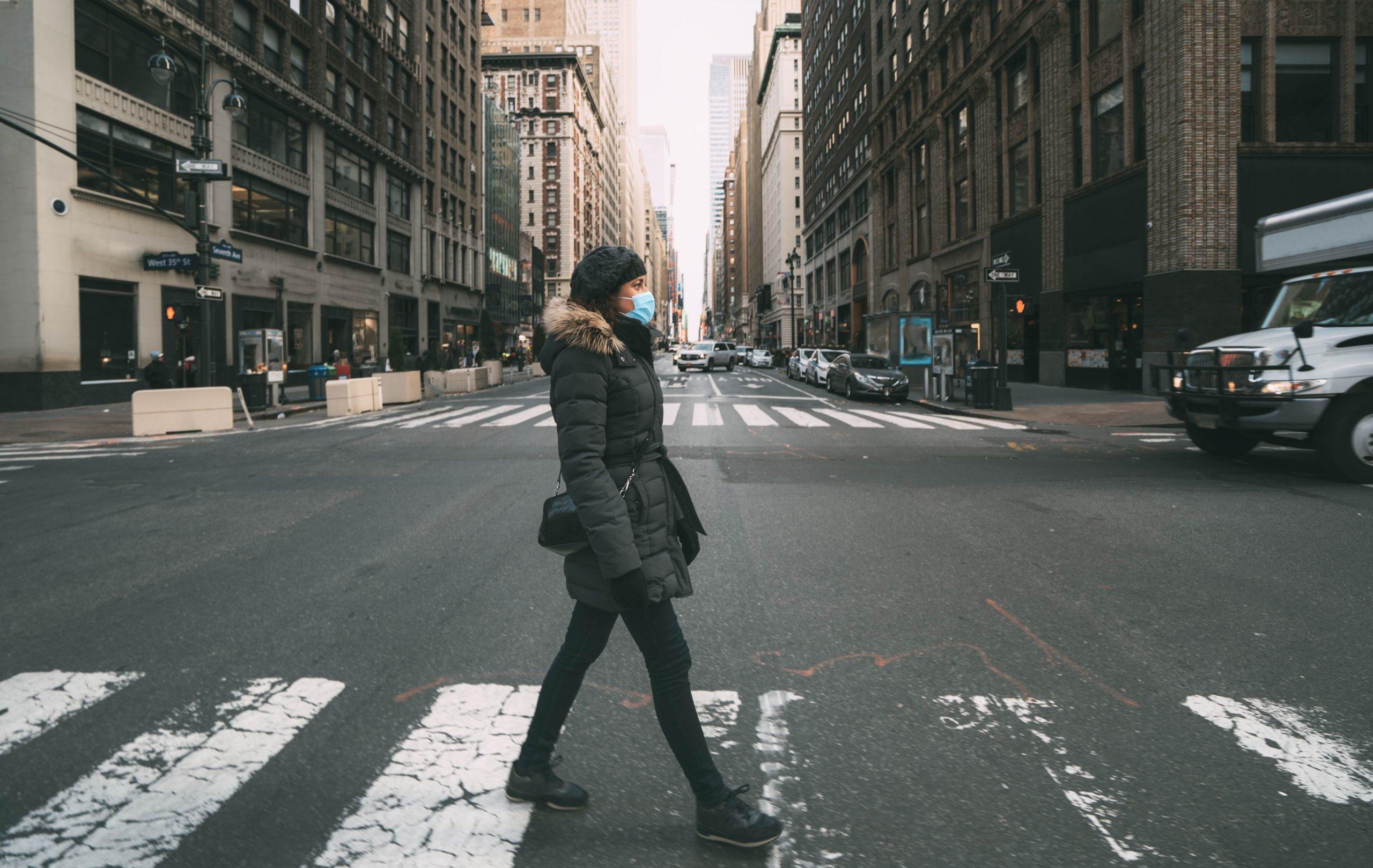 femme portant un masque traversant un passage piéton