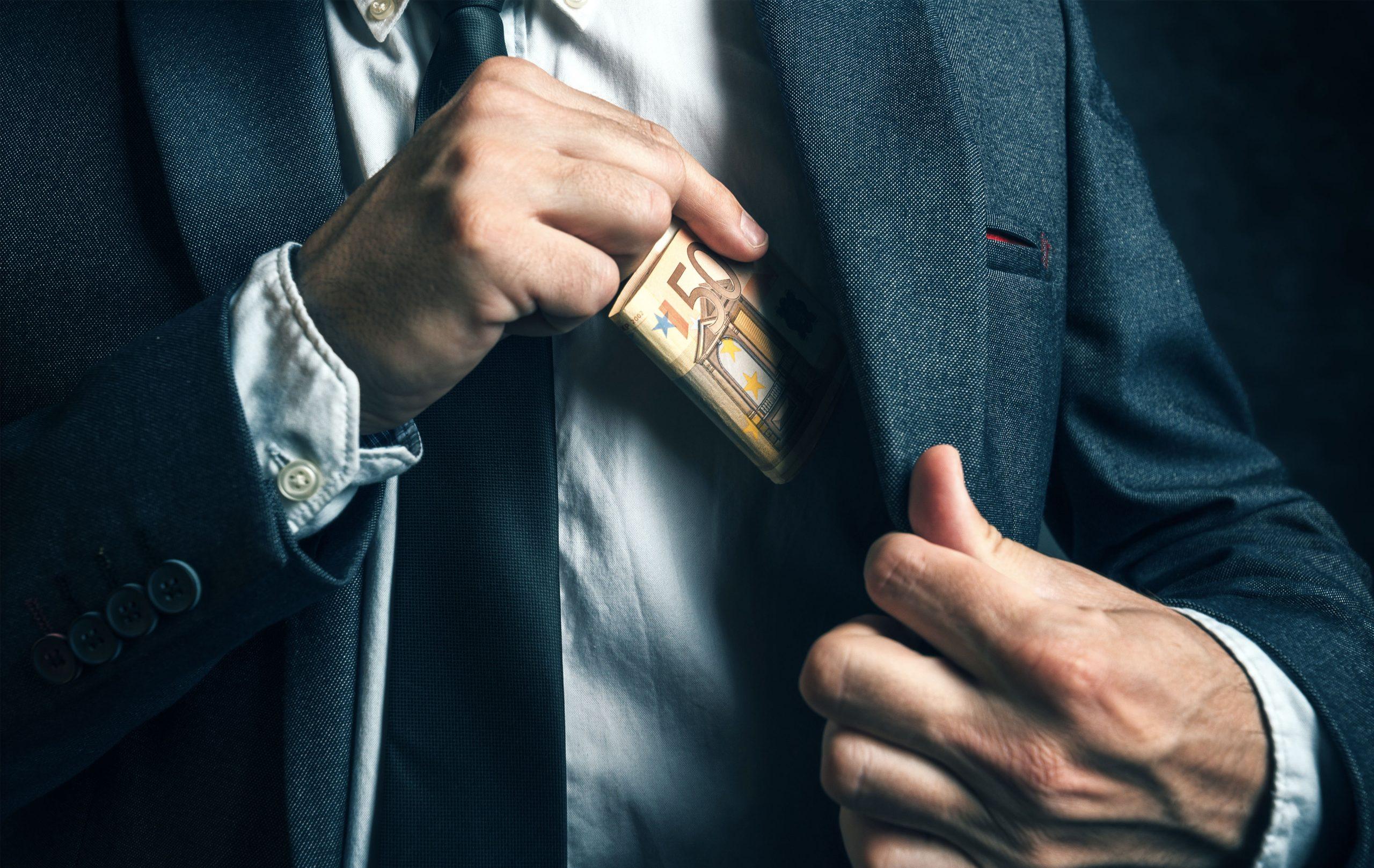 homme mettant de l'argent dans sa veste
