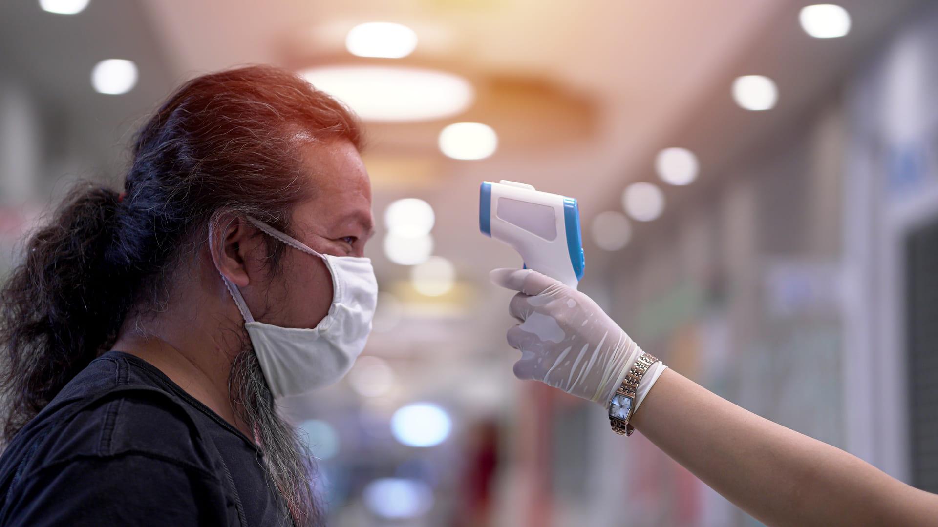 main mesurant la température corporelle d'un homme avec une caméra thermique