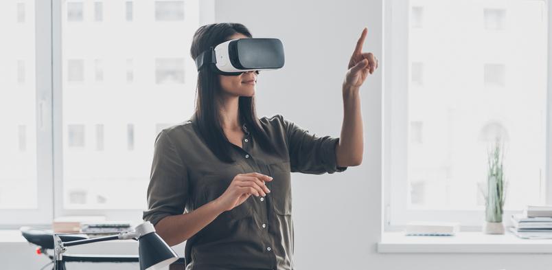 Femme avec un casque de réalité virtuelle dans un bureau